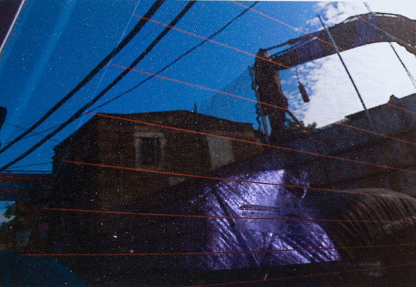Stuart Shils: Germantown Avenue Building Beyond Coulter Street, Reflected Through a Rear Window of a Car (2009) Archival pigment print