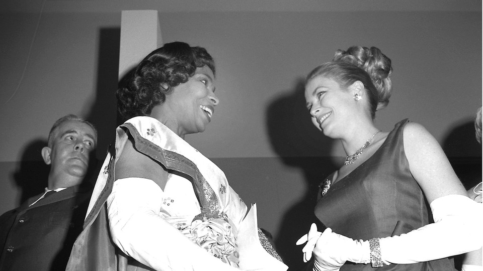 Marian Anderson (left) speaks with Grace Kelly at the Crystal Ball at the Philadelphia Museum of Art, as Kelly's husband Rainier III, Prince of Monaco, looks on