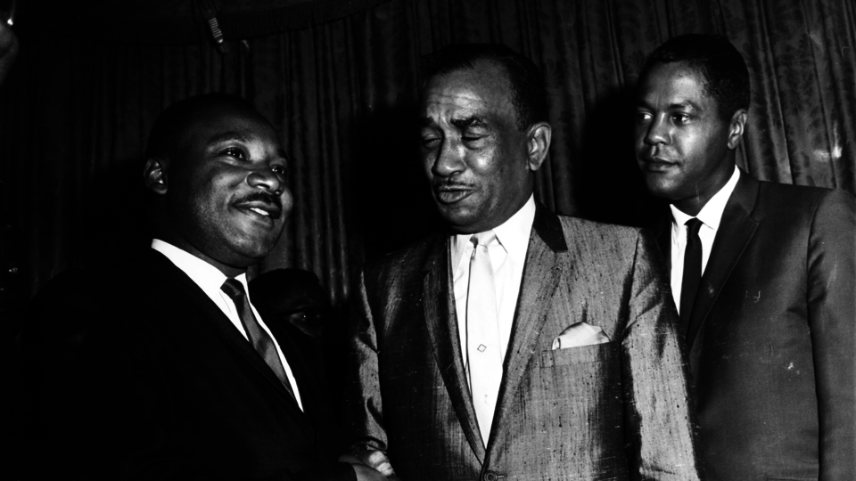 Dr. Martin Luther King, Jr. and Cecil B. Moore shaking hands as Georgie Woods watches on at the Bellevue-Stratford Hotel during a press conference to discuss plans for a rally at Girard College, Philadelphia